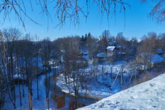 View of village through tree branches in winter. A view of the village through tree branches in winter Royalty Free Stock Photography