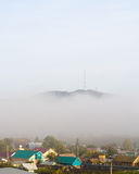 View of the village under hill in fog Stock Photos