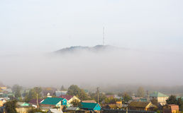 View of the village under hill in fog Stock Photo