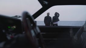 View from the vintage car on couple by the sea.  stock footage