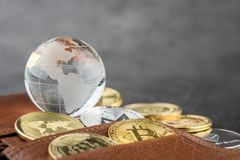 View of Virtual cryptocurrency concept image. View of different kind of metal bitcoins in brown leather wallet and glass globe .Concept image for cryptocurrency stock photo