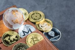 View of Virtual cryptocurrency concept image. View of different kind of metal bitcoins in brown leather wallet and glass globe .Concept image for cryptocurrency royalty free stock photos