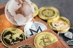 View of Virtual cryptocurrency concept image. View of different kind of metal bitcoins in brown leather wallet and glass globe .Concept image for cryptocurrency royalty free stock images
