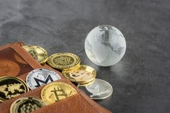 View of Virtual cryptocurrency concept image. View of different kind of metal bitcoins in brown leather wallet and glass globe .Concept image for cryptocurrency stock image