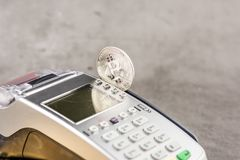 View of Virtual cryptocurrency concept image. View of metal bitcoin with POS terminal.Concept image for cryptocurrency.Concept of bitcoin payment and stock image