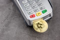 View of Virtual cryptocurrency concept image. View of metal bitcoin with POS terminal.Concept image for cryptocurrency.Concept of bitcoin payment and stock photos