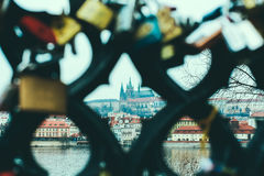 View of Vltava river and Prague castle through the fence with love locks. View of Vltava river and Prague castle from the other side of the river through the Royalty Free Stock Image