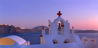 Volcanic caldera on Santorini island over the bell tower of the Royalty Free Stock Images
