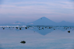 The view of the volcano Agung from Gili Trawangan in the early morning at low tide. Views of the Agung volcano with reflection in the water off the island of Stock Photos