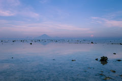 The view of the volcano Agung from Gili Trawangan in the early morning at low tide. Views of the Agung volcano with reflection in the water off the island of Stock Photo
