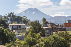 View of volcano in Guatemala. View of volcano from rural Guatemalan town. Partly cloudy blue sky above with houses, green bushes, and trees Stock Photos