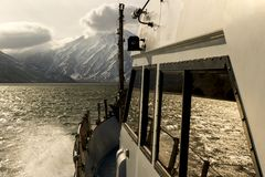 View of Volcano Vilyuchinsky from bow of the cruise ship. Sunbeams penetrate the sunset clouds. Kamchatka Peninsula. View of Volcano Vilyuchinsky from bow of royalty free stock photography