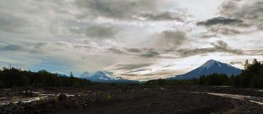 View of volcanoes: Ostry Tolbachik, Klyuchevskaya Sopka, Bezymianny, Kamen from river Studenaya at dawn. Kamchatka Stock Photo