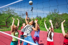 View through volleyball net of playing teens Royalty Free Stock Photography