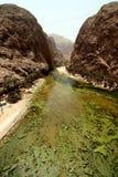 View of Wadi Shab. Looking along the water towards large boulders at Wadi Shab in Oman Royalty Free Stock Photography
