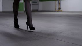 View of walking female`s legs in black stockings and high heels in garage. View of attractive female`s legs wearing black stockings and shoes with high heels and stock video