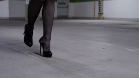 View of walking woman`s legs in black stockings and high heels in parking lot. View of attractive woman`s legs wearing black stockings and shoes with high heels stock video footage