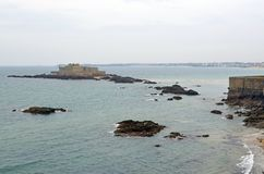 View from the wall of the old city with granite buildings of Saint-Malo in Brittany, France. Saint Malo beach, sea and fort stock image