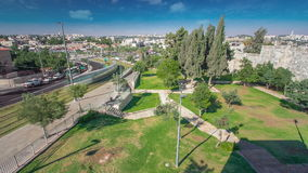 View from the wall to Jerusalem Old Town timelapse with Modern tram and traffic on the road. Jerusalem, Israel. Top view from the wall to Jerusalem Old Town stock video