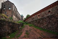 View of the walls and buildings inside the fortress. Inside the fortress, buildings and walls are visible to the left and to the right. Up comes a dirt path Stock Images