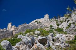 View of walls and tower of Saint Hilarion Castle, Northern Cyprus. View of walls and tower of medieval Saint Hilarion Castle in front of blue sky on Kyrenia stock photos