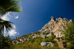 View of walls and tower of Saint Hilarion Castle, Northern Cyprus. View of walls of medieval Saint Hilarion Castle and palms in front of blue sky with white stock photo