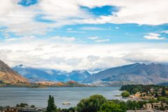 Beautiful view of Wanaka alpine lake and ski resort town. View of Wanaka lake and alpine resort town with the mountain range in the background on a cloudy summer Royalty Free Stock Photography