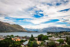 Wanaka lake and alpine resort town in New Zealand. View of Wanaka lake and alpine resort town with the mountain range in the background on a fair summer day in Stock Photography