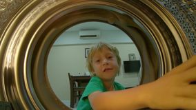 View from the washing machine as a little boy puts dirty clothes into it.  stock video footage