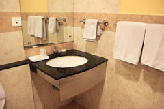 View of Washroom Corner. Modern bathroom furnished with wash basin, mirror and towel rods Royalty Free Stock Image
