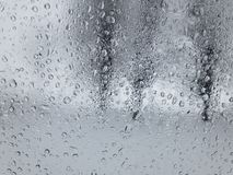 View through water dropson a weeping car window on threes. In winter season stock photos