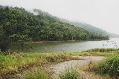 View of water reservoir for hydroelectric dam located in Malaysia. Lush vegetation,cloudy foggy mountain and dam wall in the stock image