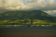 A view from water of Saint Kitts Island with mountain tops covered with clouds Stock Photo