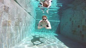 View from water on the young sports man floating under water in the pool stock video footage