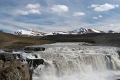 View on waterfall in arid barren dry landscape with partly snow capped mountains in the horizon - Iceland royalty free stock photo