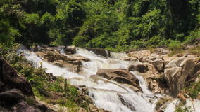View of waterfall cascade among rocks in tropical park stock video
