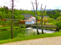 View on waterfall, mill in white building, pedestrian bridge in Park Postojna jama near Postojna Cave. Famous attraction in Slovenia Stock Photo