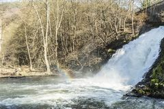 View of a waterfall with a rainbow reflected in the water with an arid vegetation in the background in the small city of Spa Belgi royalty free stock photography