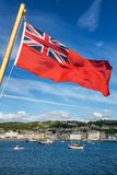Red Ensign and Oban harbour. View of the waterfront with boats, the harbour and the historic buildings of Oban Scotland. The Red Ensign flag is in the foreground stock images