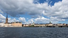 View of waterfront buildings in Stockholm, Sweden. Viewed from the water under a cloudy blue sky in a travel concept Stock Photos