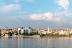 View of  waterfront on Canakkale, Turkey. View of Canakkale, Turkey. Reflections in the water of houses and mosque Royalty Free Stock Photography