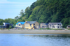 View of  Waterfront Community. A view of a small waterfront community of homes at low elevation beside a hill under blue skies Royalty Free Stock Photos