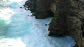 View of waves breaking under cliffs near Uluwatu temple stock footage