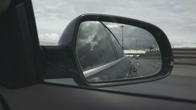 View of the way in the side mirror. Of a car stock video footage
