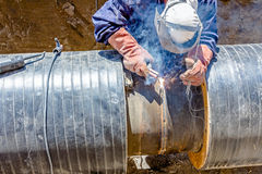 View on welder until welding pipeline. Welder is in trench working hard, arc welding pipeline Stock Photography