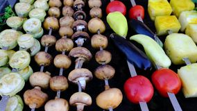 A view of well-cooked mushrooms and vegetables on skewers, lying on a brazier. Street food. A view of well-cooked appetizing mushrooms and various vegetables on stock video