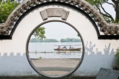 The view  of the West Lake in traditional garden. The picture was taken on May 4th,2012 Hanghzhou, China. The lake viewed through the round Chinese traditional Royalty Free Stock Photography