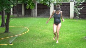 The view of the wet pregnant woman running from the sprinkler. stock video footage
