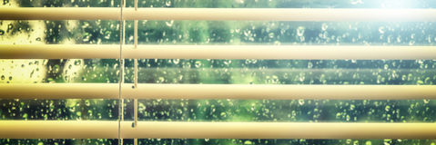 View of wet window with rain drops through blinds Stock Photo