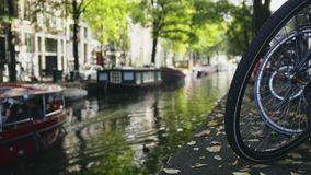 View of wheel of bicycle on the Amsterdam canal, next to floats tour boat, sunny european autumn stock video footage